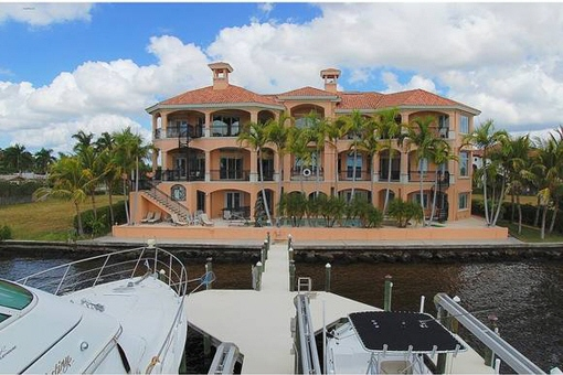 Two-story home in a prime location on the water with boat dock, pool room and much more in Cape Coral